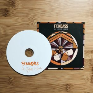 Finkbass' CD Cover and CD All Engines Running lying on a wooden surface